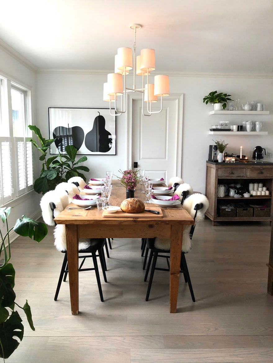 farm table in dining room with black chairs, pendant lighting and modern art