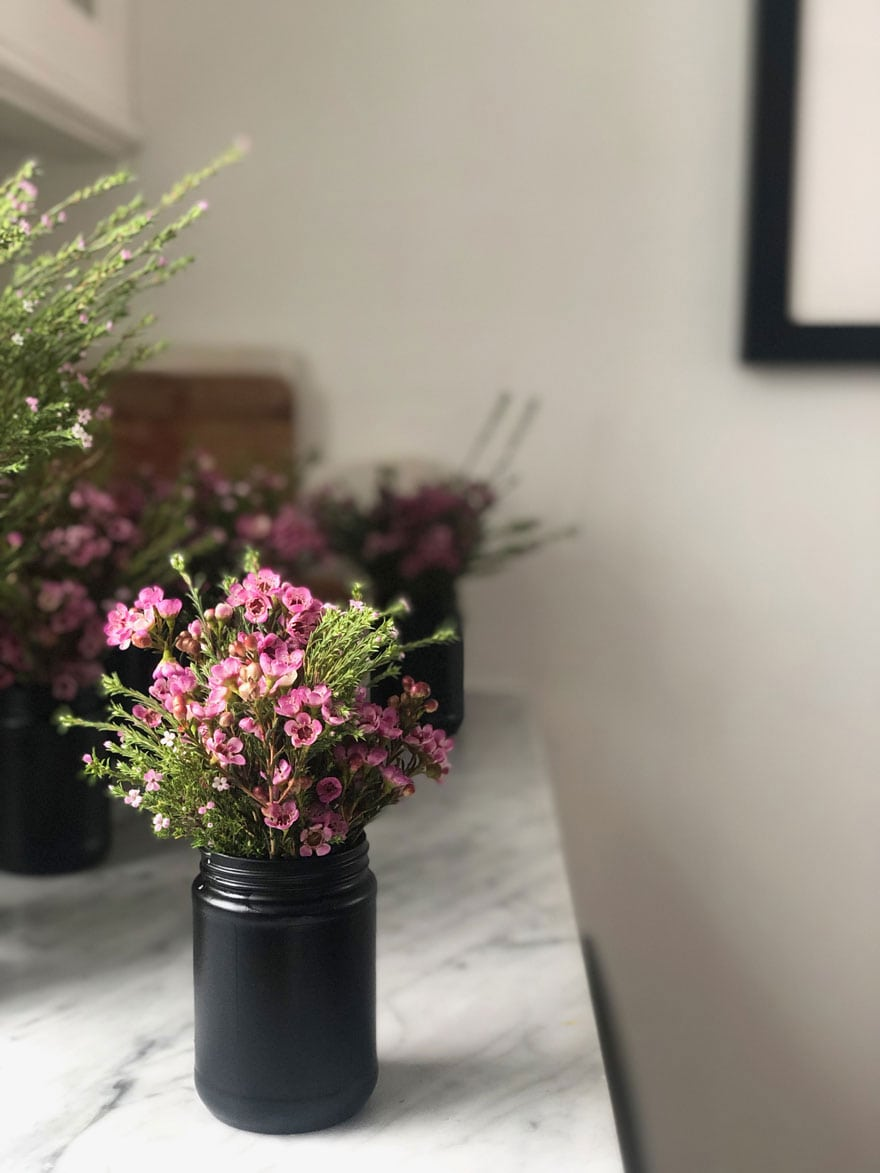 small jar with pink flowers on marble counter top