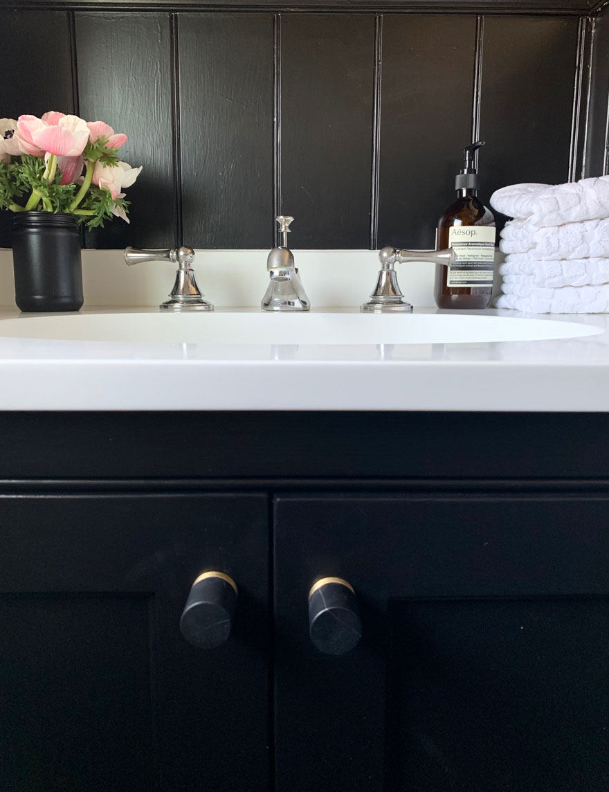 black vanity with white sink, anemones, soap, white towels