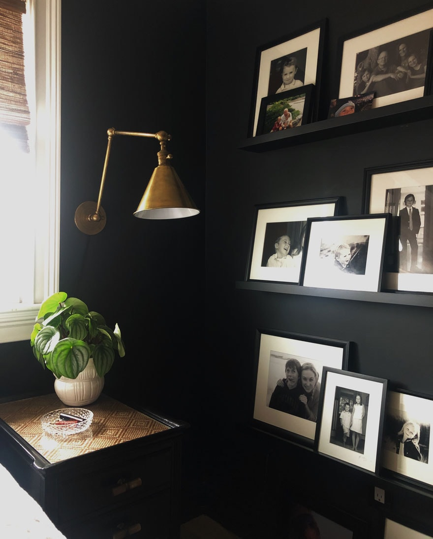 photos on ledges on black walls, brass sconce, plant