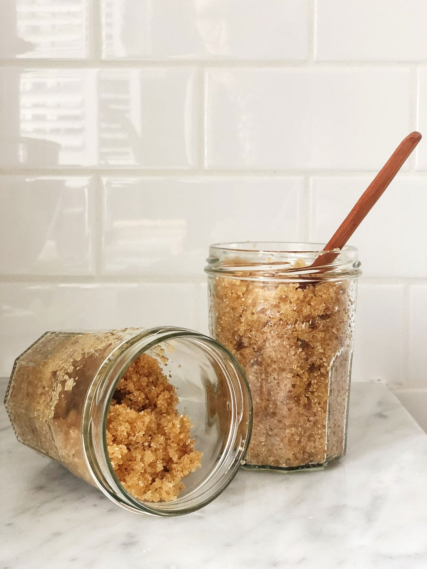 2 jars with a wood spoon and brown sugar mixture on white subway tile background
