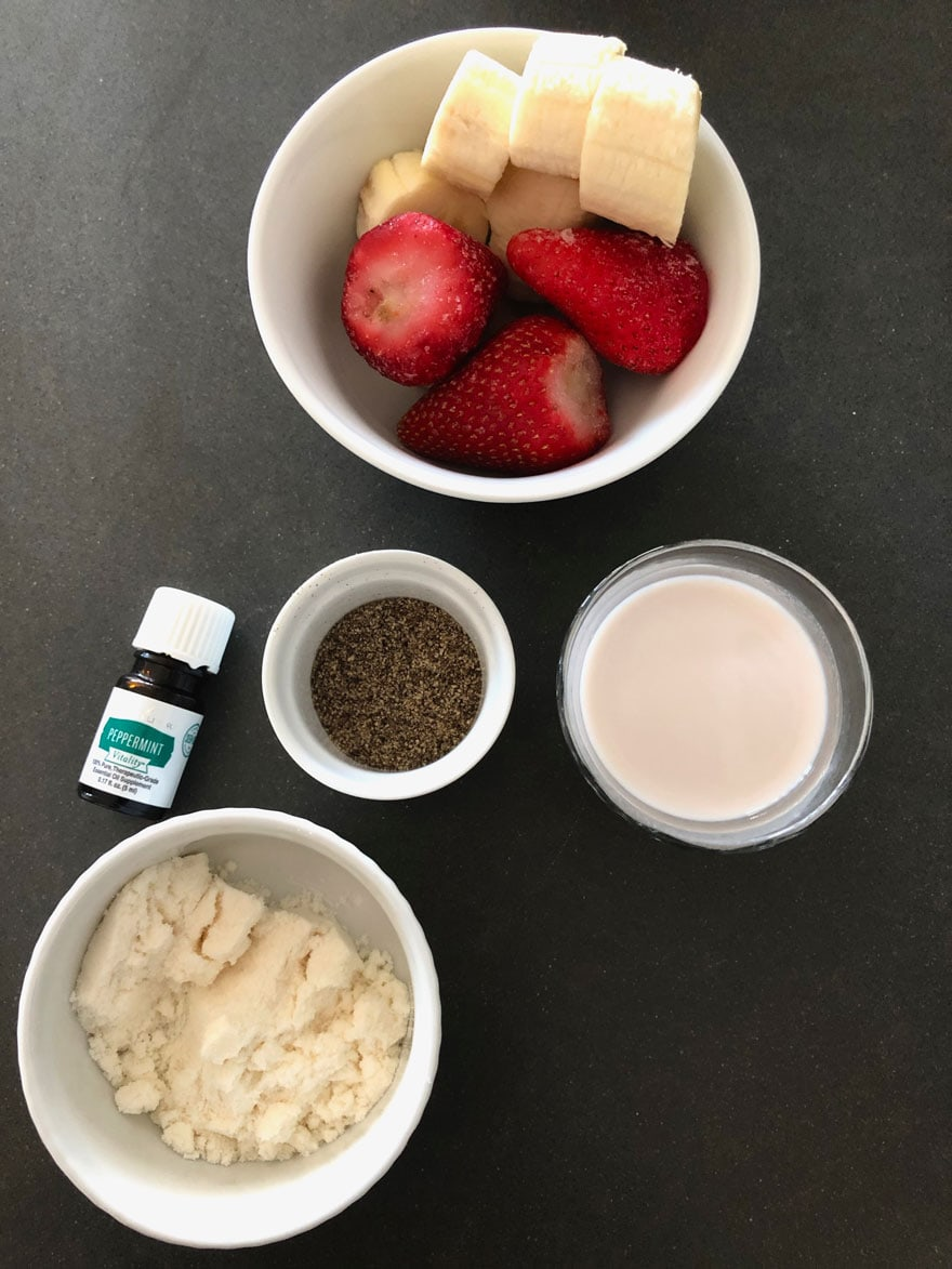 ingredients in bowls, strawberry, banana, peppermint essential oil bottle