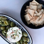 green olives, goat cheese in dish with a bowl of crackers in black bowl