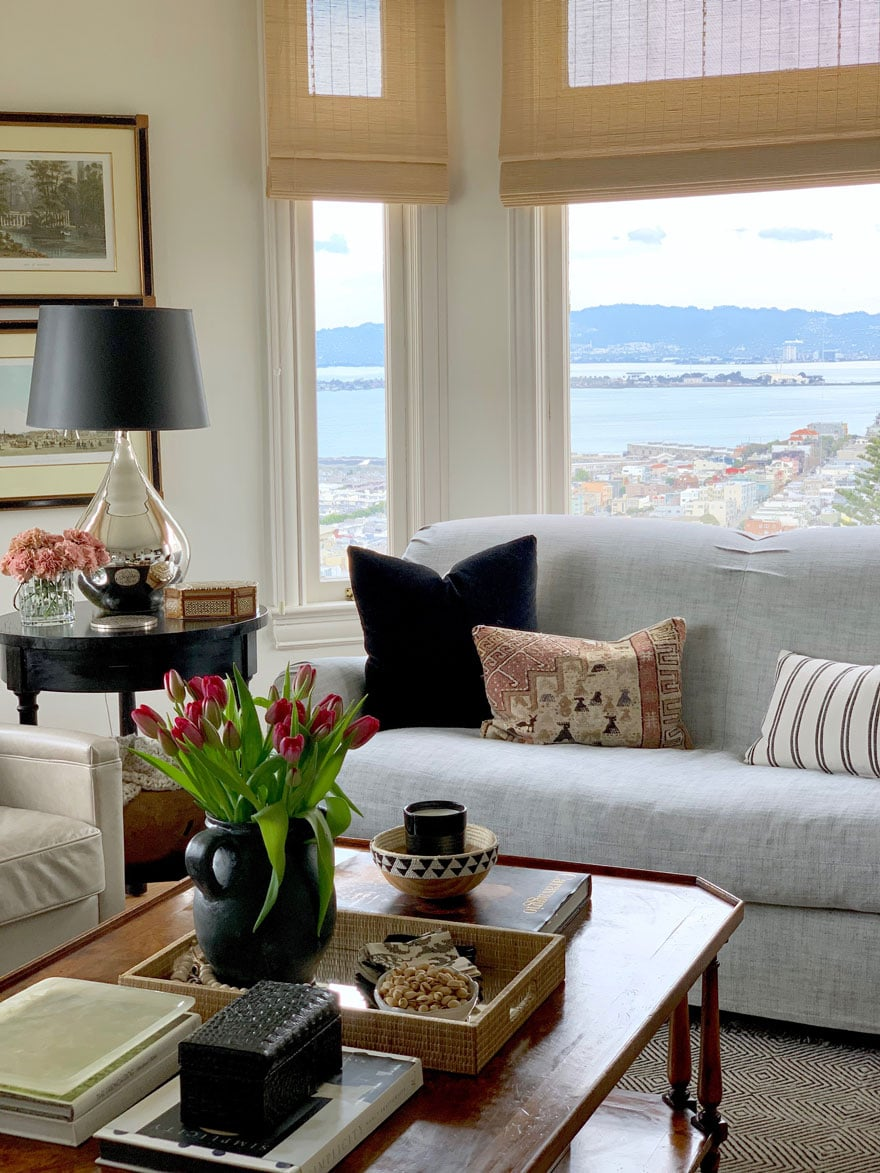 sofa with pillows, table with lamp black lamp shade, tulips in black vase, views