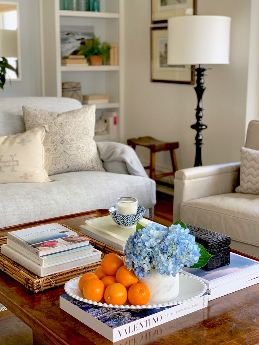 coffee table with oranges, hydrangea. sofa, lamp, art