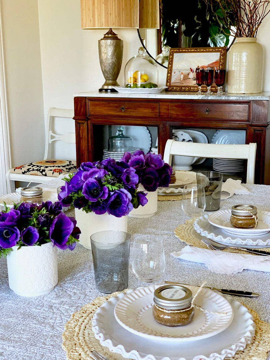 table with flowers, dish hutch with miter and lamp