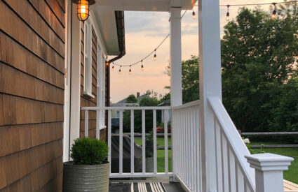 side porch, light, planter, boxwood, striped rug, railing painted white, sky with trees