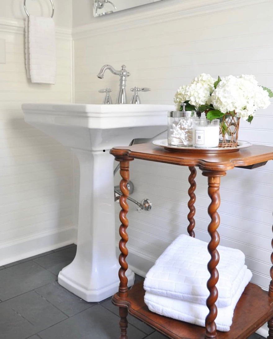 antique table, white sink, white towels, slate floor