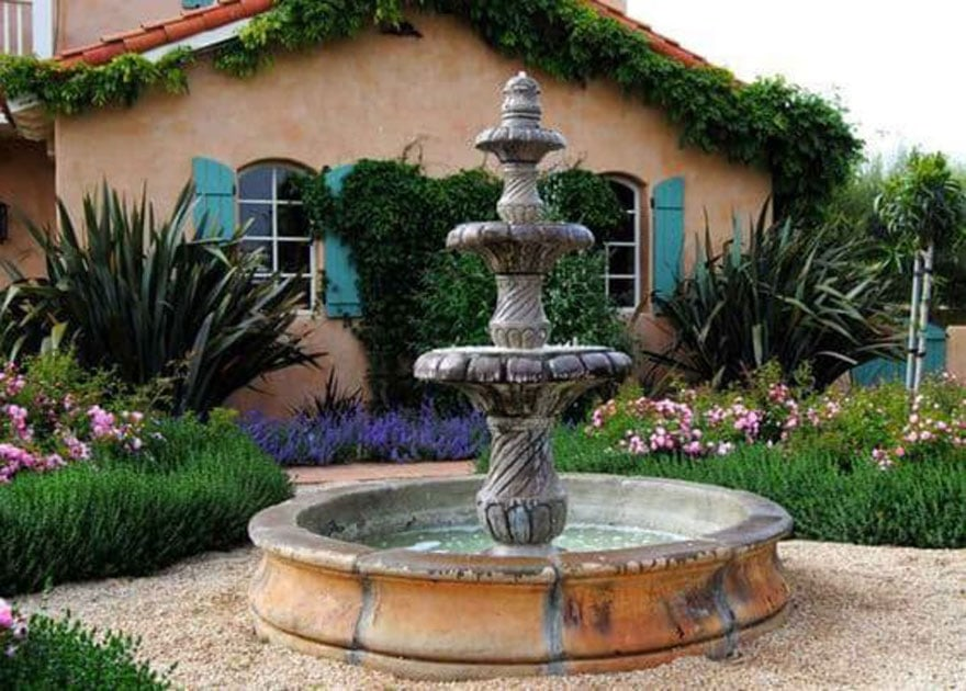 fountain with gravel walkway and house with shutters