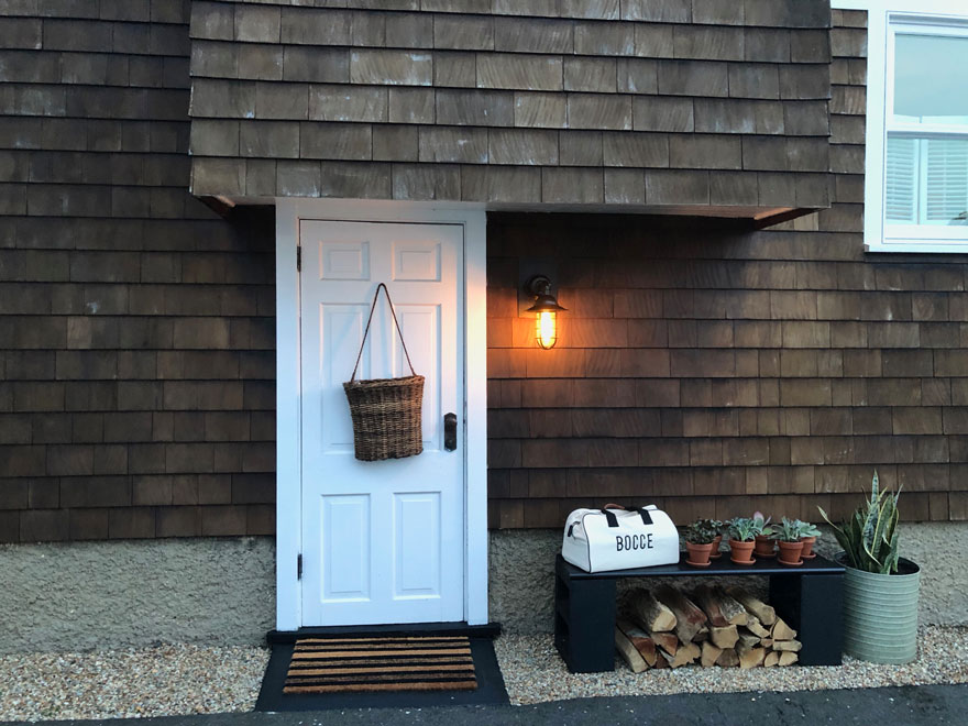 door, basket on door, bench, bag with bocce on it, light, plants, stacked wood, doormat
