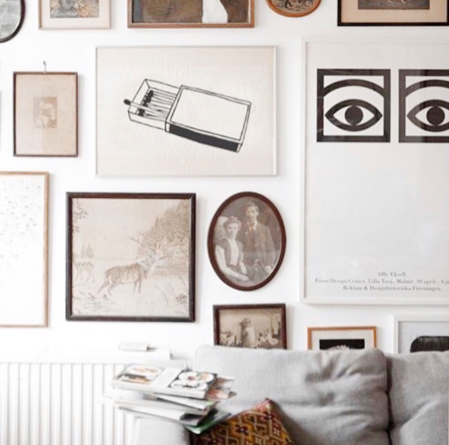 photogrpahs, art, drawings, posters on wall with sofa, pillow