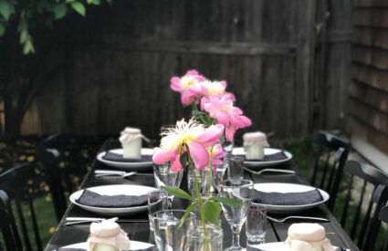 outdoor table, peonies, citronlella candles, clear glassware, bush