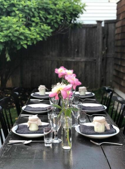 outdoor table, peonies, citronlella candles, clear glassware, bush