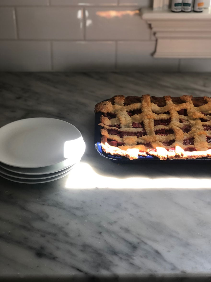 pie on countertop with white plates