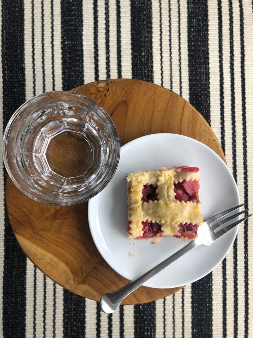 pie on white plate with fork, glass of water on round stool on striped rug