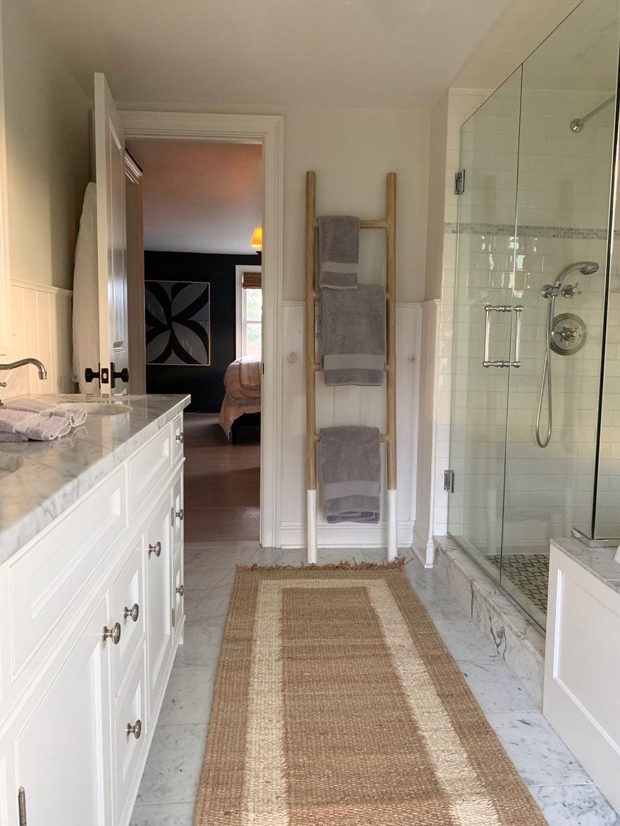 teak towel ladder in bathroom with jute rug runner on marble