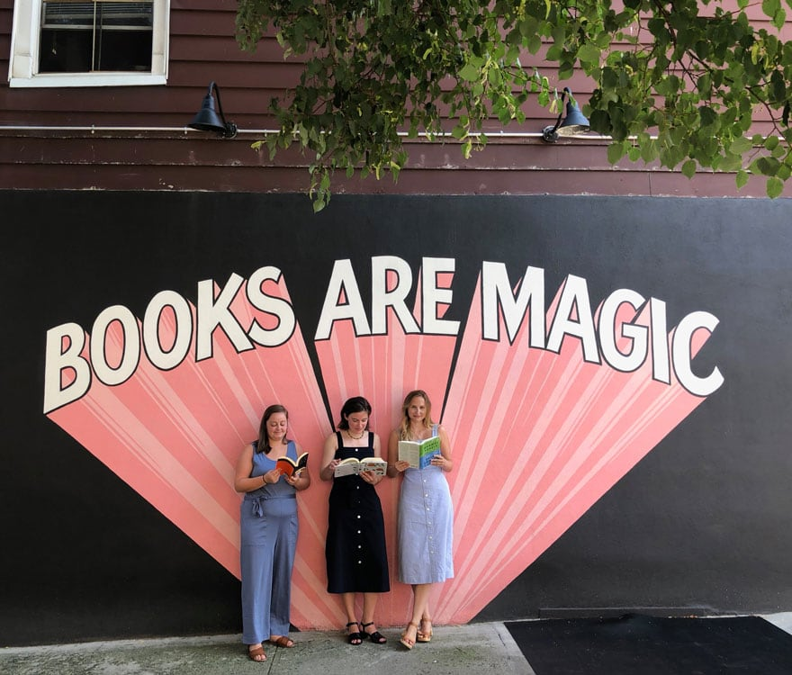 3 girls in front of wall mural on street with books in hand