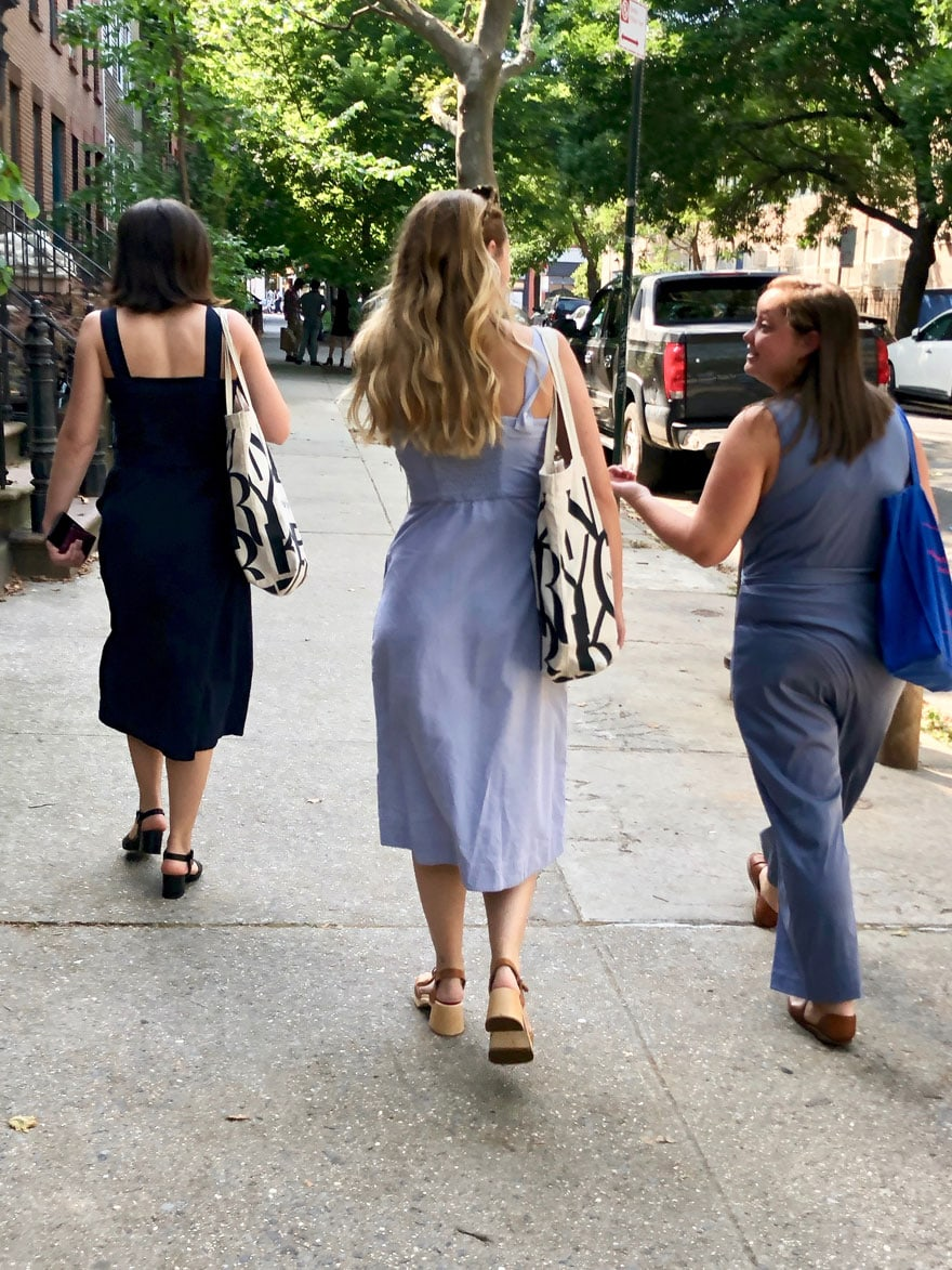 girls walking on a Brooklyn street with tote bags