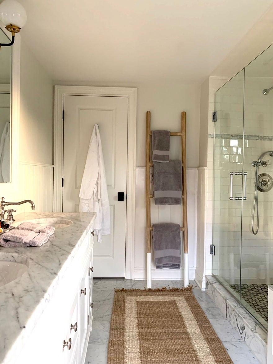 marble countertops, teak ladder, rug runner, robe, shower