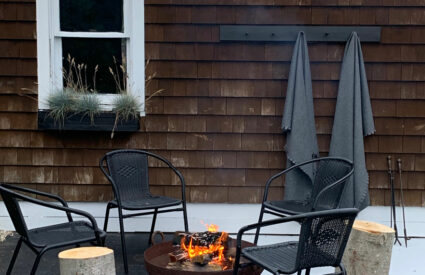 chairs, fire pit, tree stumps, window, throws on hooks on side of garage