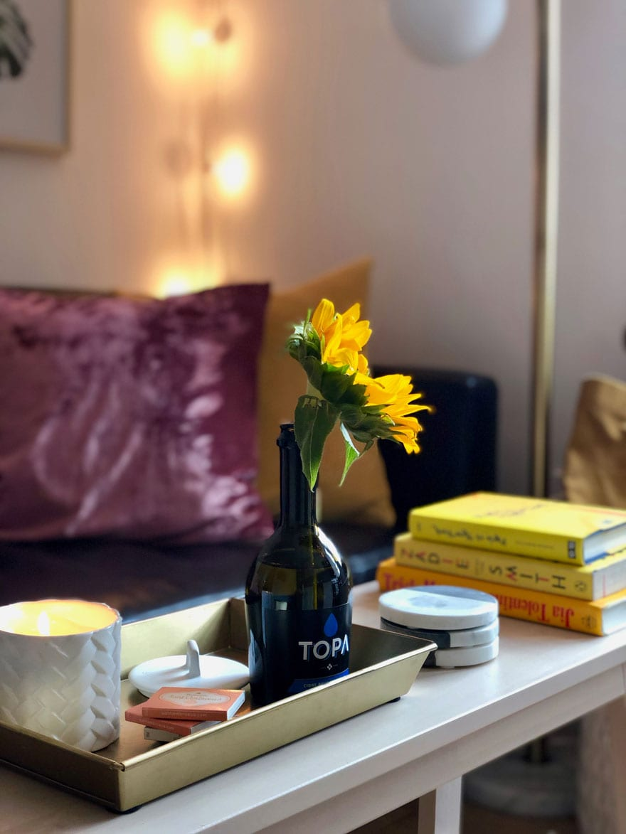 flower in bottle, books, candle, pillows