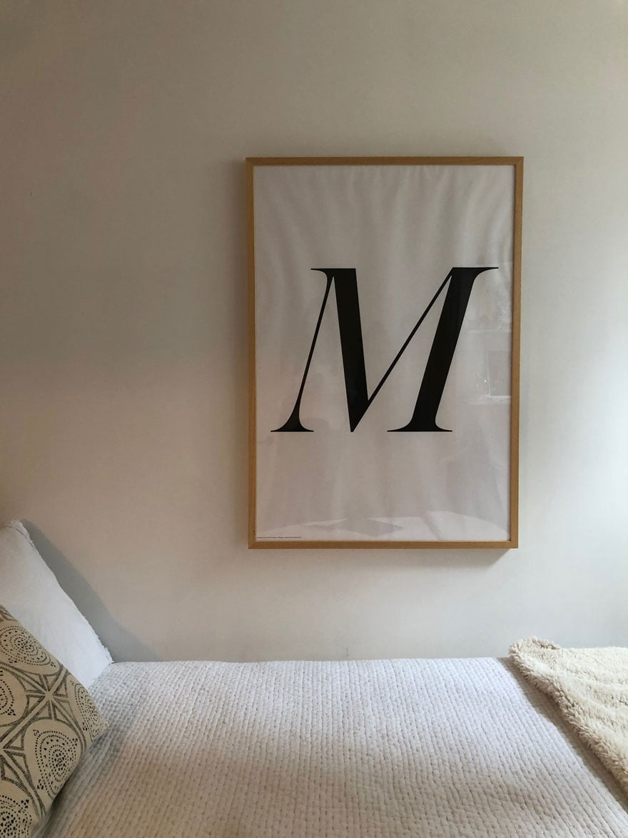 large M poster in white bedroom