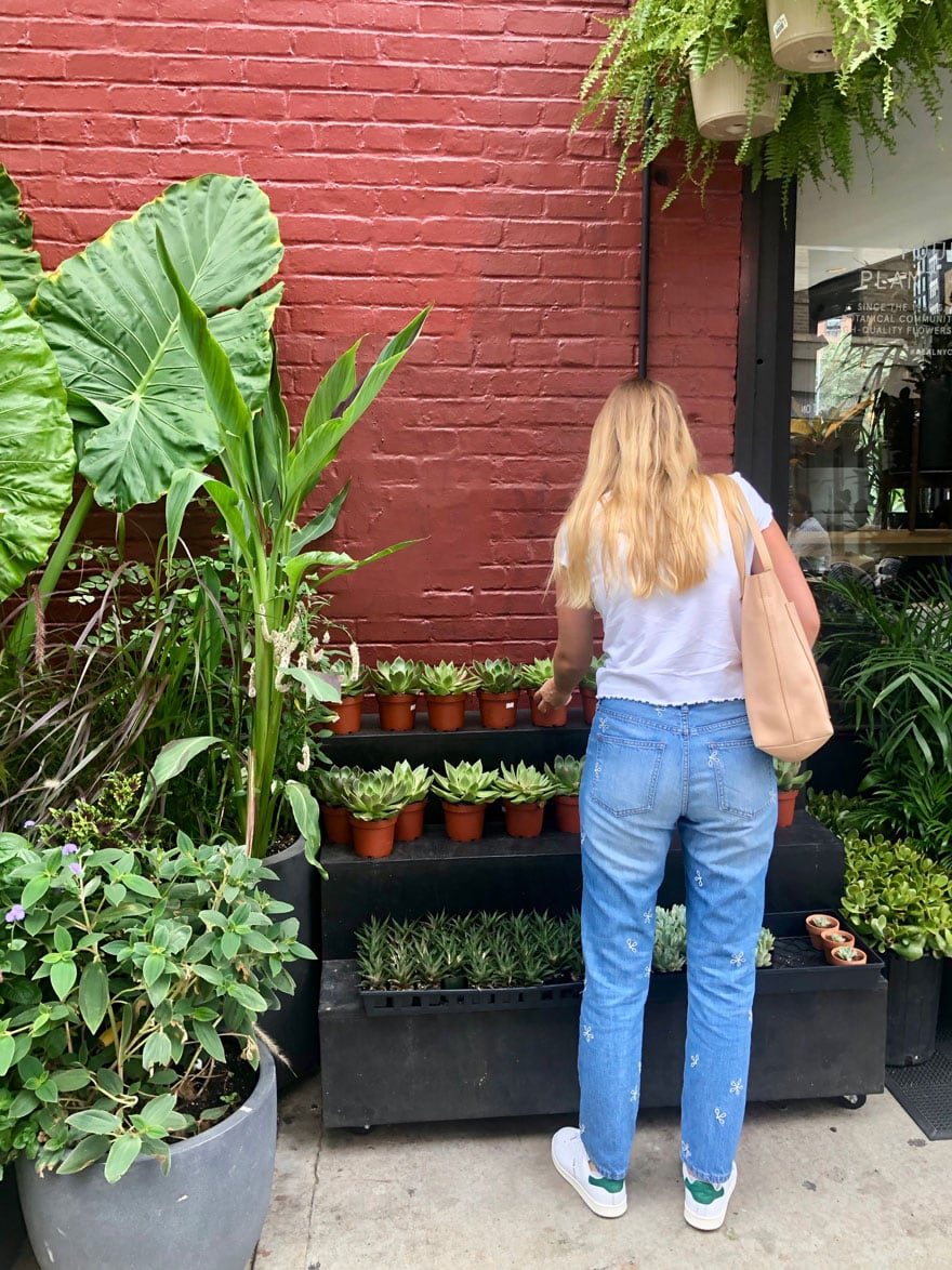 girl in jeans at plant store with red painted brick wall