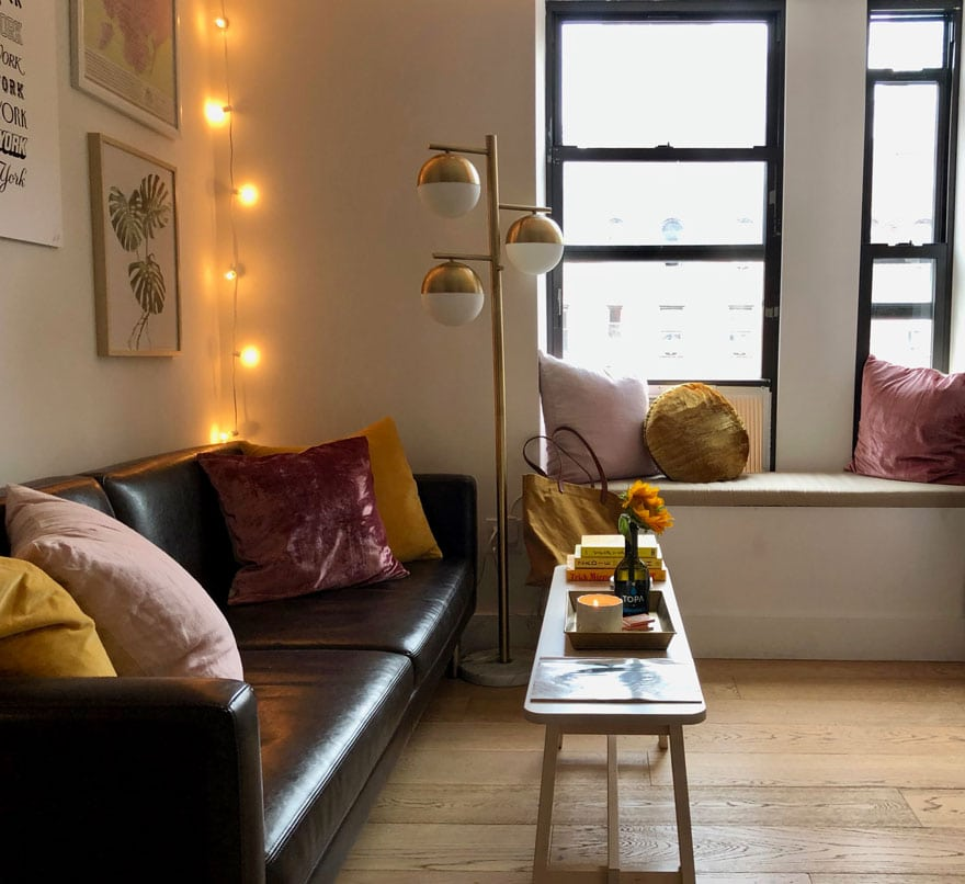 apartment living room with sofa, window seat, pillows, lamp, string lights, bench