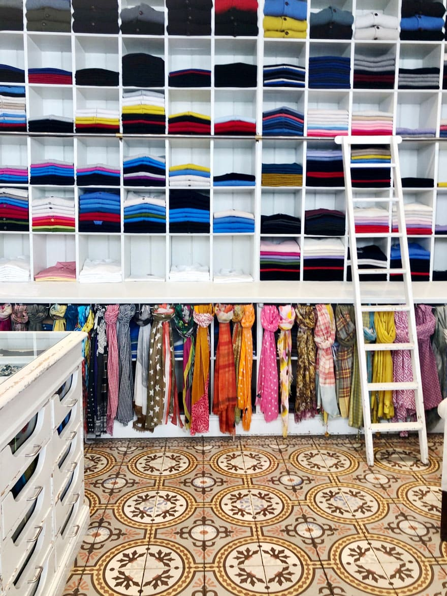 sweaters on white shelves, scarves tied and tiled floors