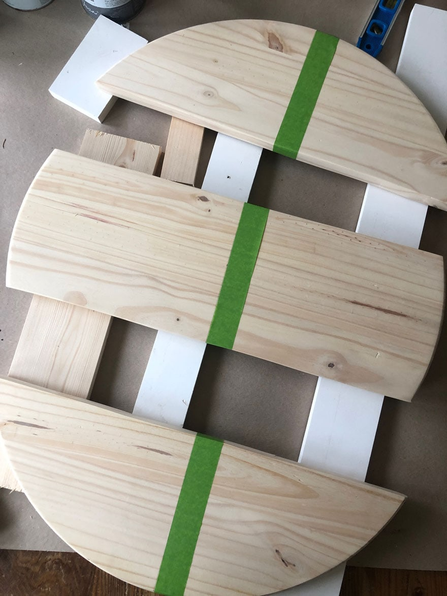 three pieces of wood with green tape