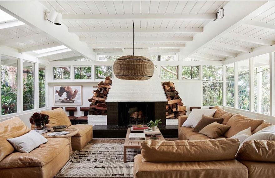 white painted brick feireplaecm leather sofas, pendant light, stacked wood