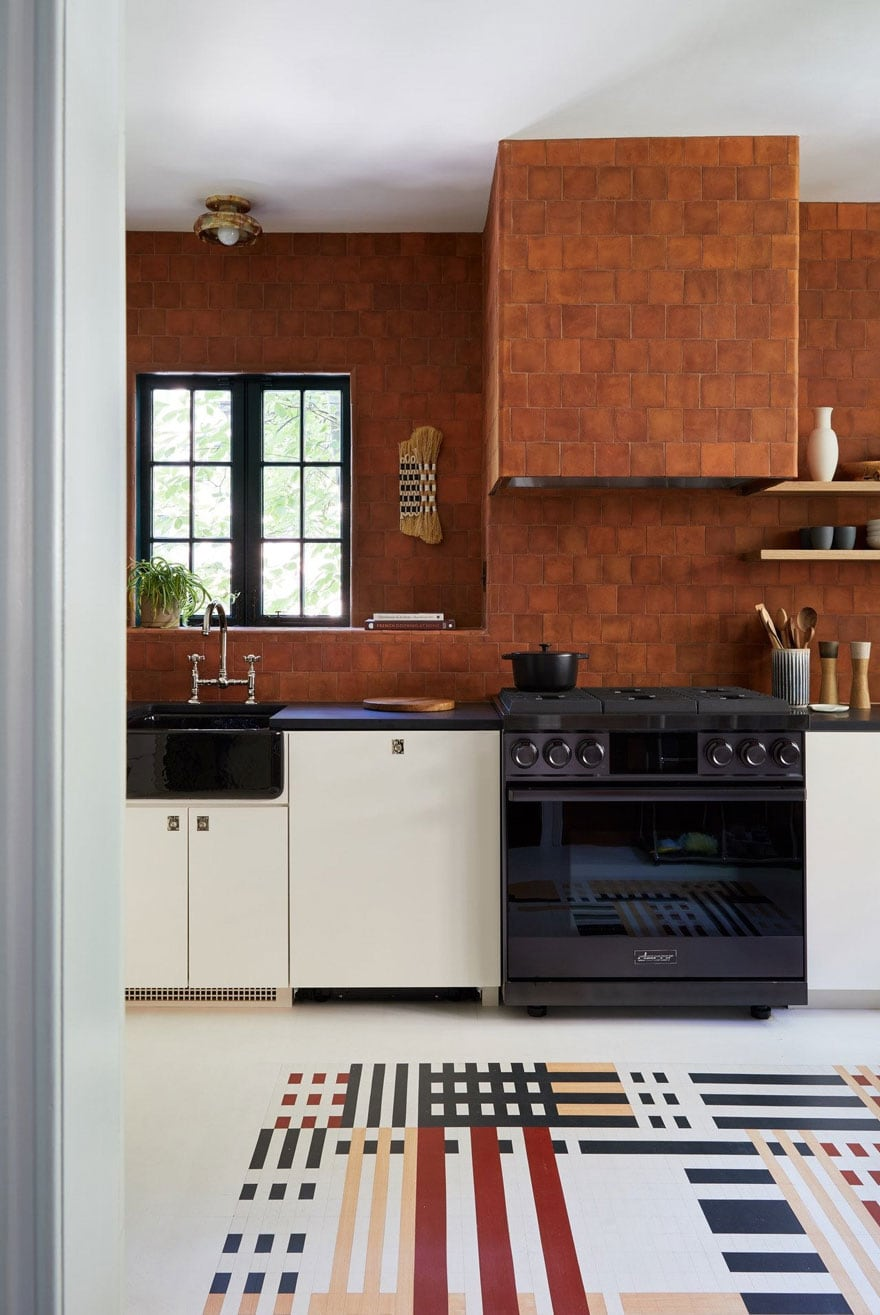 kitchen with terra-cotta color tile, black stove, painted floors