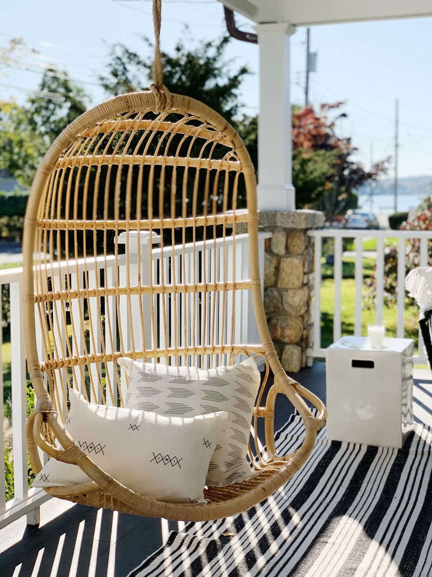 pillows on hanging chair on a porch