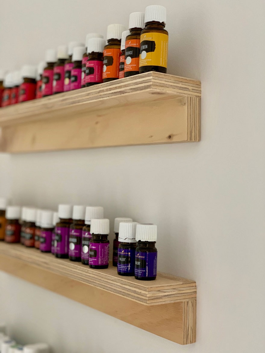 shelves on white wall with bottles of oils