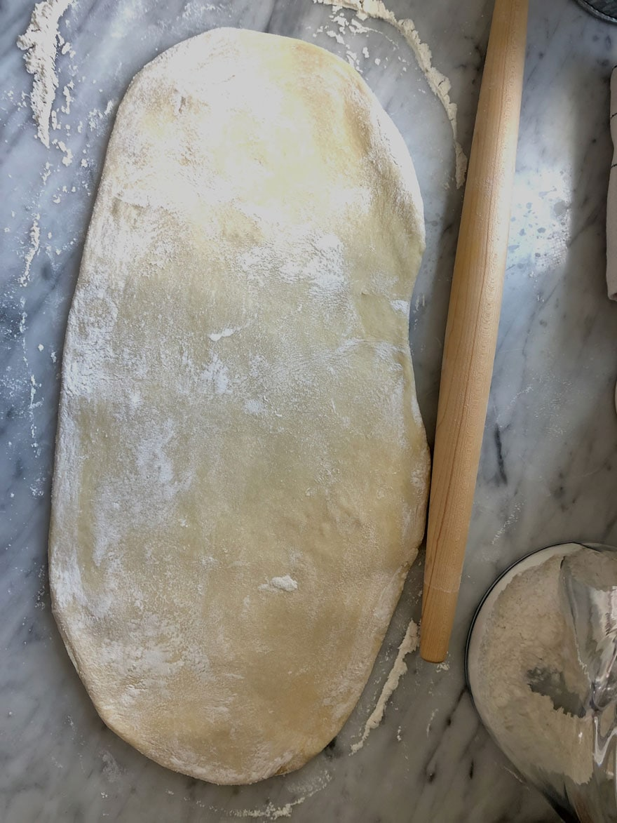 rolled out dough on marble with rolling pin