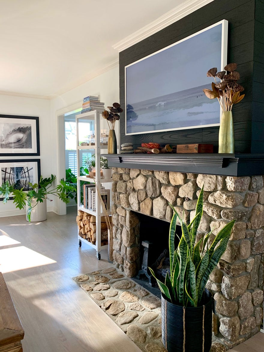 stone fireplace in living room with wood floors