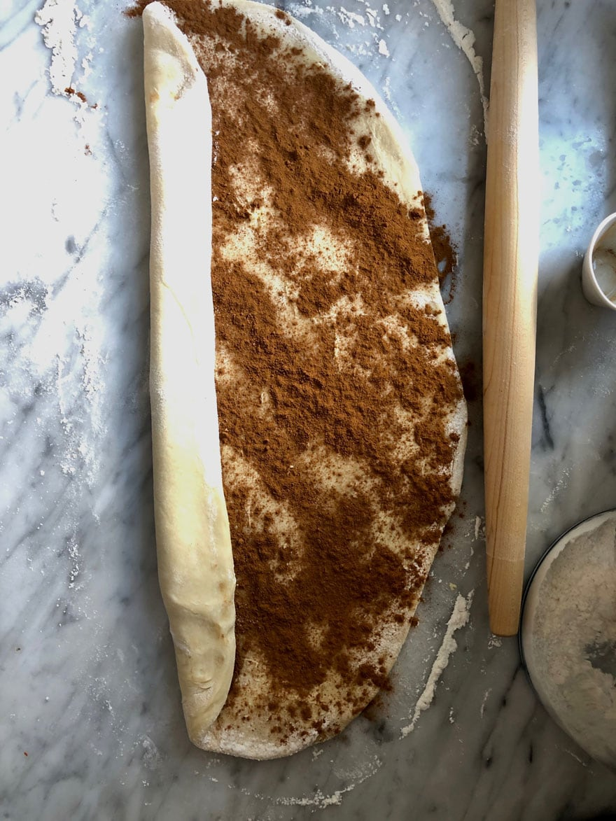 cinnamon on dough about to be rolled up