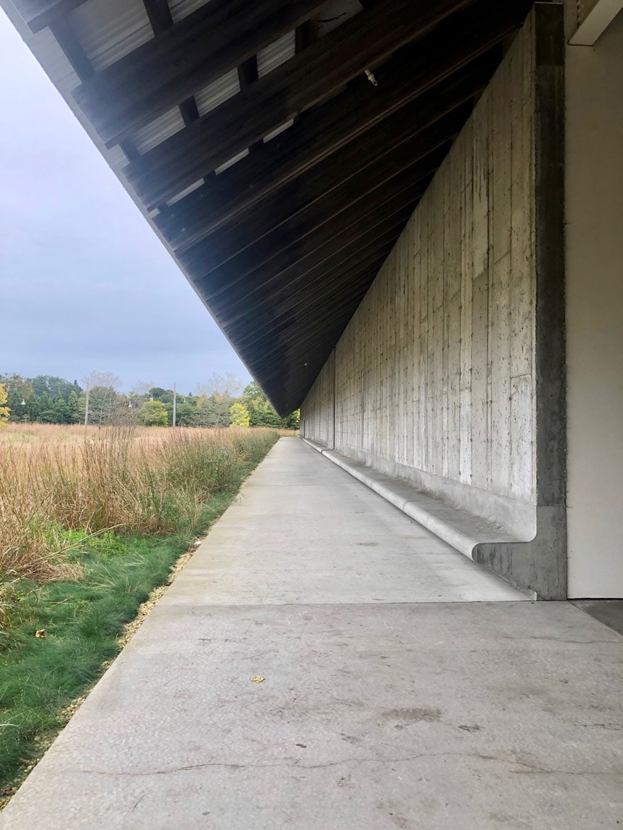 concrete benches on large building with meadow of grasses