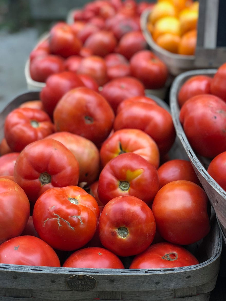 red heirloom tomatoes at a farm stand