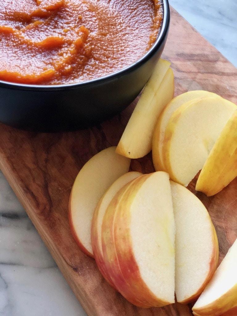 bowl of pumpkin butter apples on wood board