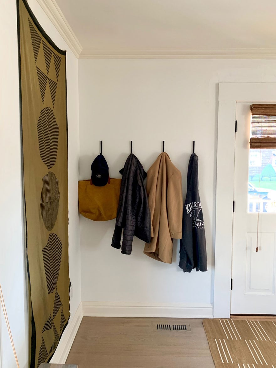 hooks on wall with hat, bag, coats