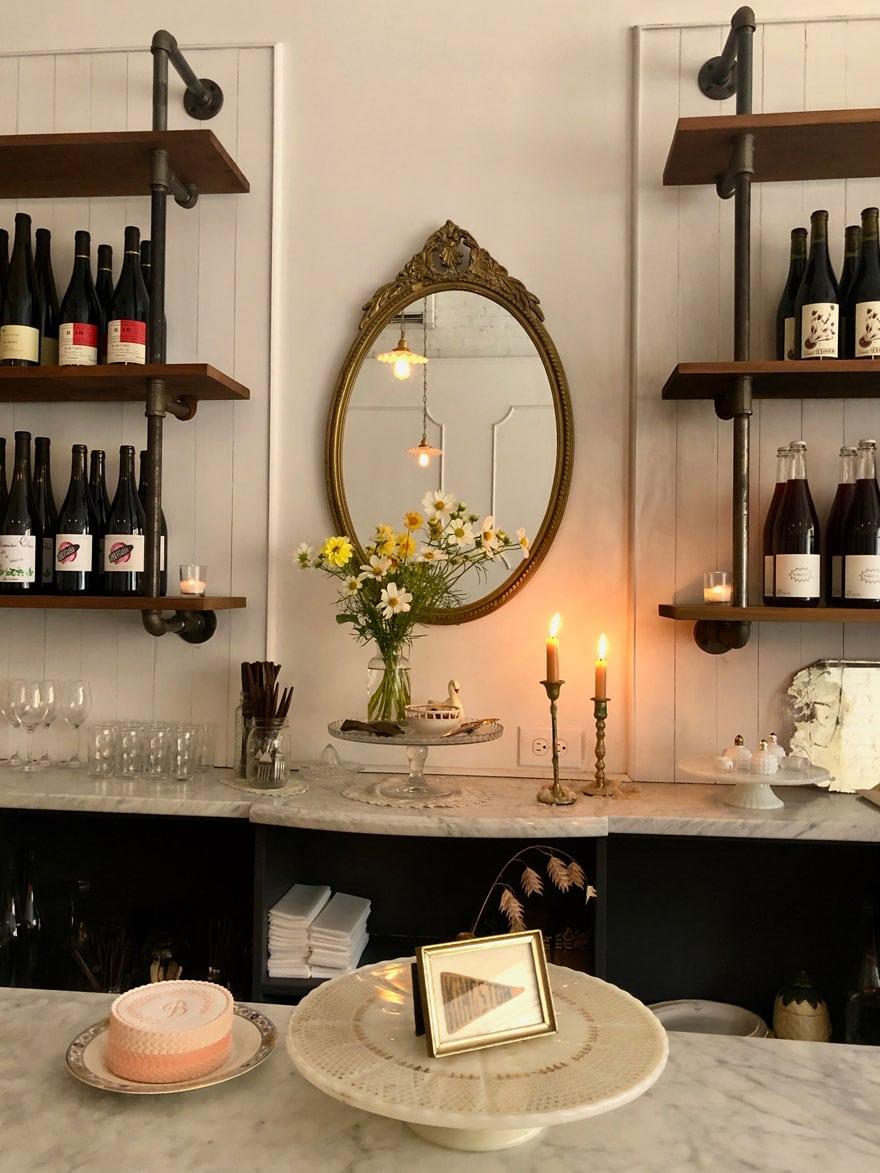 vintage mirror, flowers, candles on marble, glassware, wine bottles
