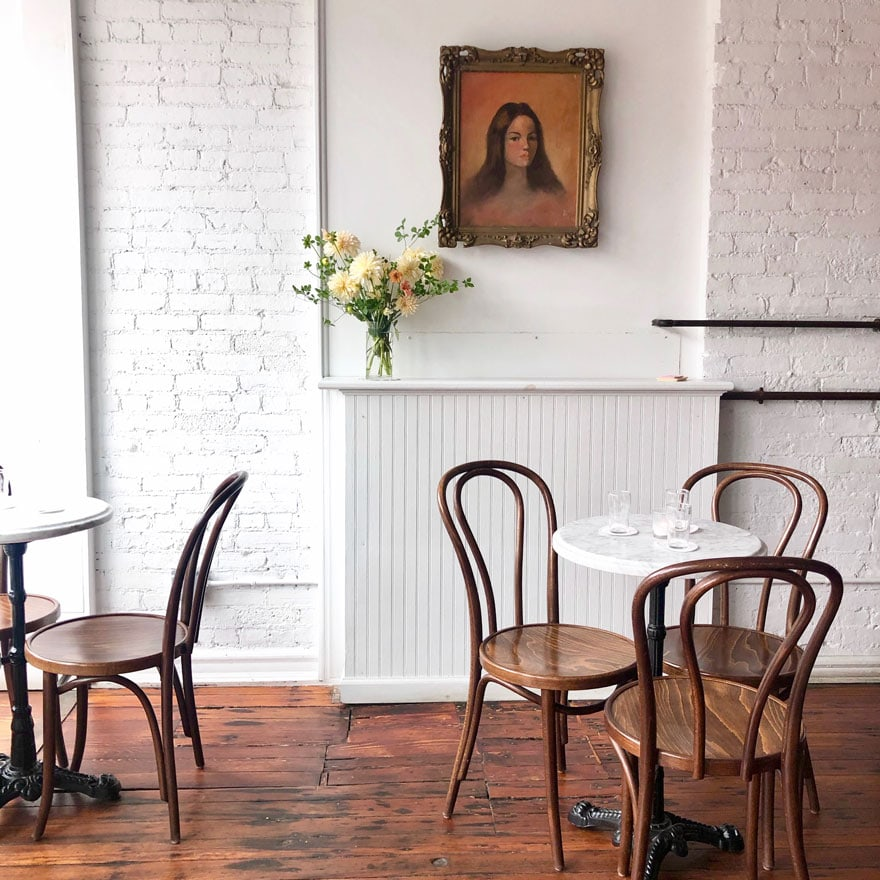 cafe chairs, marble tables, white walls, painitng, vase with flowers