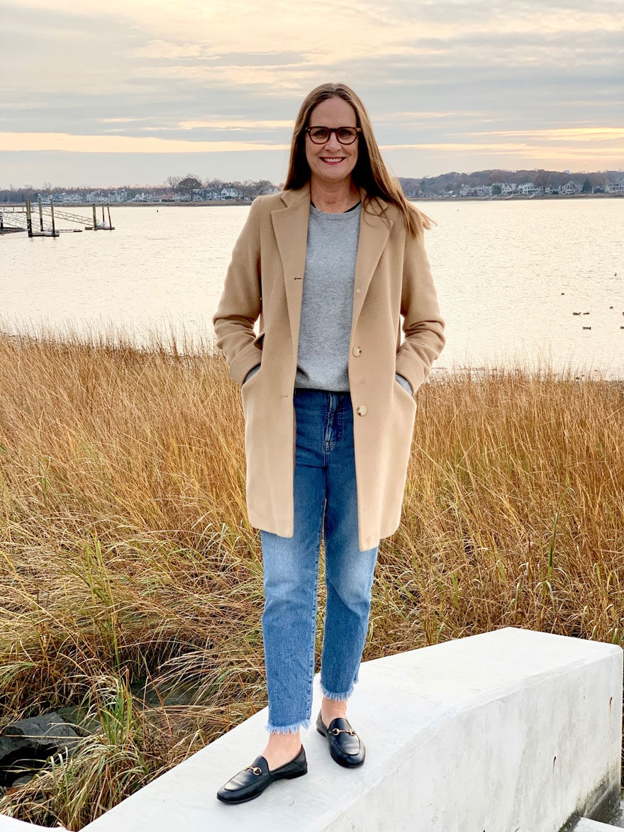 woman wearing jeans and camel coat at waters edge