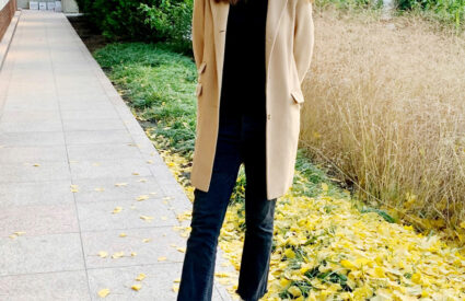 woman wearing black with camel coat and white booties