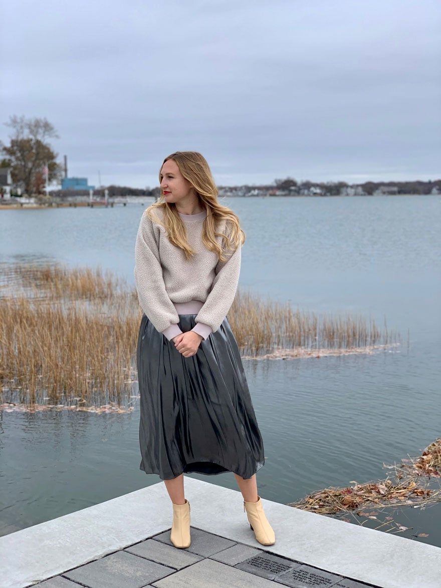 woman standing on edge of water in fall wearing silver skirt, tan sweater