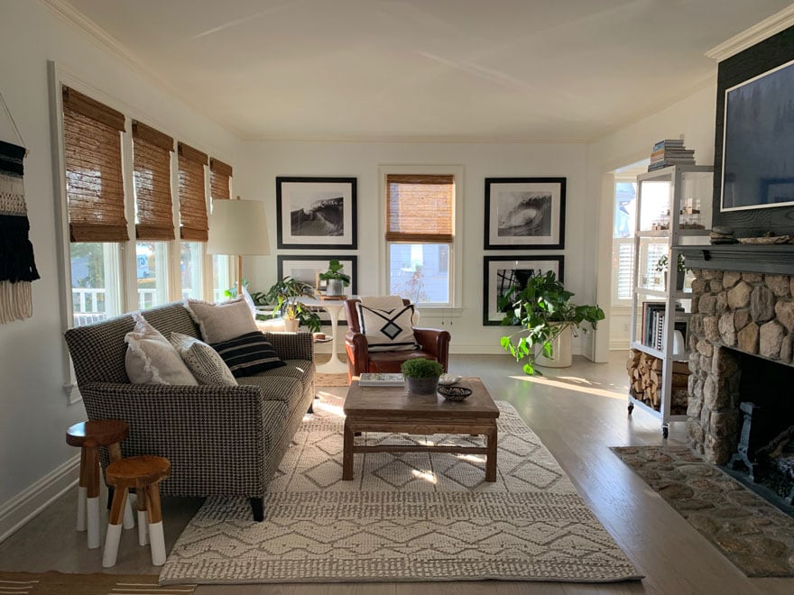 living room with woven wood shades rug, planrs, sofa, table