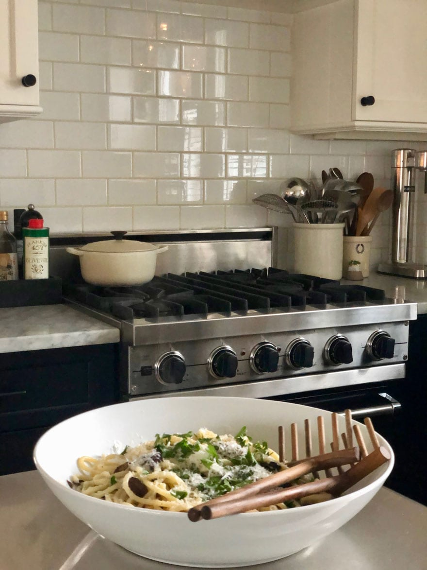 bowl of pasta with black stove and subway tile