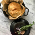 Lodge pan with bakes bread and rosemary tied to the handles lid with twine