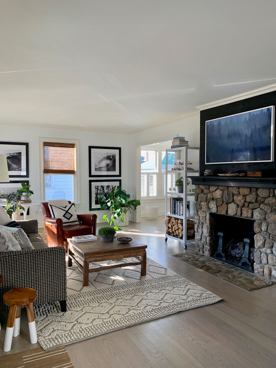 TV above stone fireplace in lving room with furniture